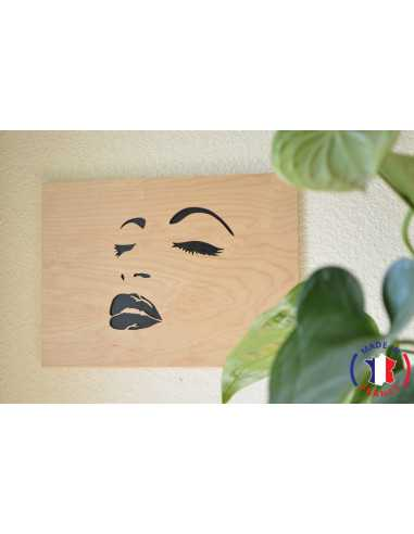 Painting of a woman's face chantourné in birch.